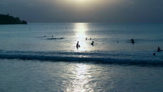People swimming in the sea while sunsetting, slow motion shot at 240fps