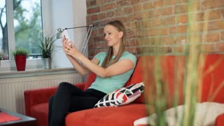 Pretty, blonde girl doing selfie on smartphone while sitting on the red sofa