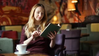 Pretty, blonde girl reading book and drinking coffee in the cafe