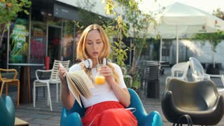Pretty, blonde girl reading book and drinking juice in the outdoor cafe