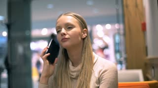 Pretty, blonde girl sitting in a cafe and answers cellphone