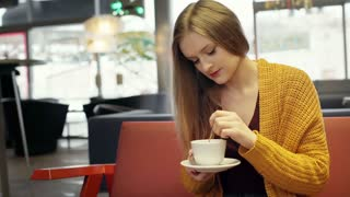 Pretty, blonde girl sitting in the stylish cafe and relaxing