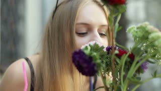 Pretty, blonde girl smelling flowers and smiling to the camera