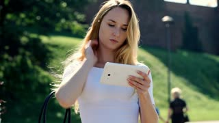 Pretty, blonde girl standing outdoors and browsing internet on tablet