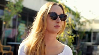 Pretty, blonde girl takes off sunglasses and smiling to the camera