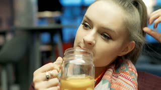 Pretty, blonde girl with ponytail relaxing in the cafe and drinking lemonade