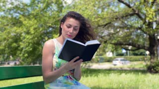 Pretty brunette sitting in the park and reading absorbing book