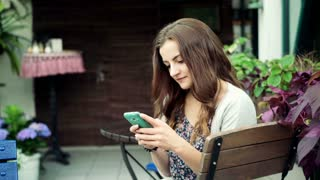 Pretty brunette sitting on the wooden chair and texting on smartphone