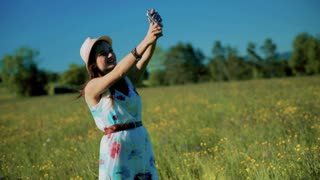 Pretty girl doing selfie on the meadow and wearing straw hat
