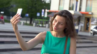 Pretty girl doing selfies on smartphone in town, steadycam shot, slow motion sho