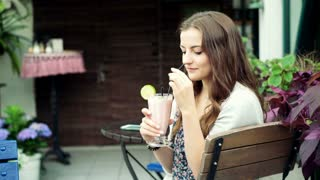 Pretty girl drinking cocktail and smiling to the camera in the cafe