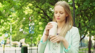 Pretty girl drinking coffee in the park and having a headache