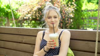 Pretty girl drinking frappe while sitting on the swing and smiling to the camera