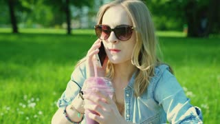 Pretty girl drinking fruity cocktail and chatting on cellphone in the park
