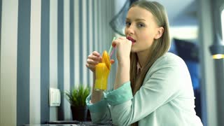 Pretty girl drinking orange juice and smiling to the camera