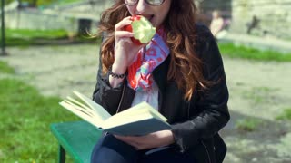 Pretty girl eating apple and reading book on boulevard, steadycam shot