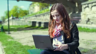 Pretty girl eating apple and using laptop on boulevard, steadycam shot