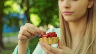 Pretty girl eating cookie with strawberries and enjoying it