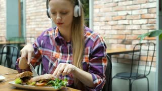 Pretty girl eating healthy lunch in the cafe and listening music, steadycam shot