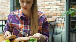 Pretty girl eating healthy lunch in the cafe and smiling to the camera, steadyca