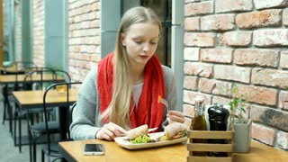 Pretty girl eating healthy lunch in the cafe and texting on smartphone