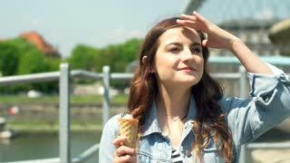 Pretty girl eating ice creams and standing next to the river