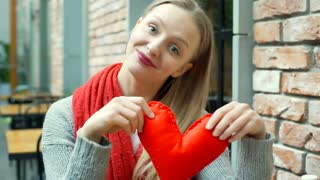 Pretty girl holding handmade heart and showing it to the camera