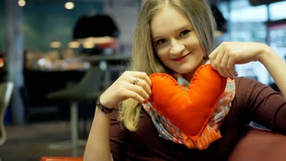 Pretty girl holding handmade heart and smiling to the camera