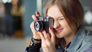 Pretty girl holding old camera and doing photos in restaurant