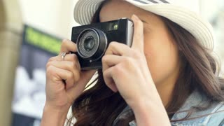 Pretty girl holding old camera and doing some photographs