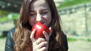 Pretty girl holding red apple and smiling to the camera