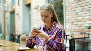 Pretty girl in checked shirt sitting in the cafe and receives good news on smart
