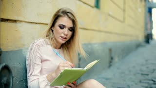 Pretty girl in elegant dress writing something in journal and smiling to the cam