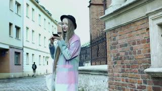 Pretty girl in pastel jacket talking on loudspeaker in the alley