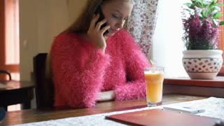 Pretty girl in pink, fluffy jersey talking on cellphone in the cafe