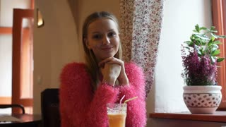 Pretty girl in pink, fluffy sweater smiling to the camera in the cafe