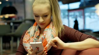 Pretty girl in ponytail using smartphone in the cafe and smiling to the camera