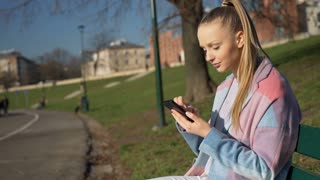 Pretty girl in stylish jacket using smartphone in the park at sunny day, steady
