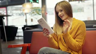 Pretty girl in yellow sweater using tablet and smiling to the camera in the cafe