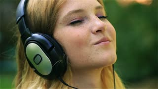 Pretty girl listening music on headphones and smiling, steadycam shot