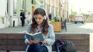 Pretty girl listening music on headphones while reading book on the bench