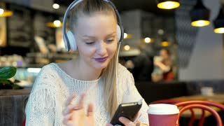 Pretty girl listening music on headphones while sitting in the bistro, steadycam