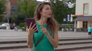 Pretty girl looking on area and using tablet, steadycam shot, slow motion shot