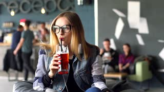 Pretty girl looking thoughtful and drinking beer in the cafe