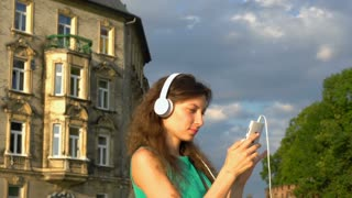 Pretty girl moving while listening music and browsing internet on smartphone