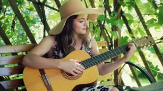 Pretty girl playing on guitar and singing in the arbor