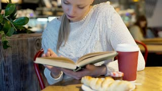 Pretty girl reading book in the bistro and smiling to the camera, steadycam shot