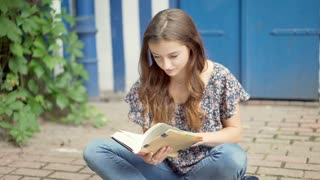 Pretty girl reading book while sitting on the ground and looking to the camera