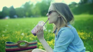 Pretty girl relaxing on the meadow in the park and drinking cocktail