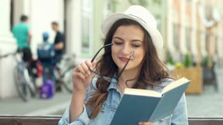 Pretty girl sitting in public place and reading absorbing book
